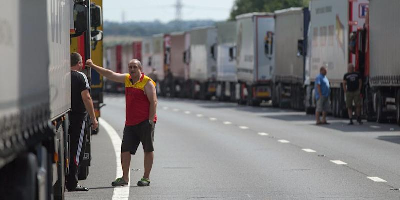 Drivers wait next to their parked lorries on the M20 motorway, which leads from London to the Channel Tunnel terminal at Ashford and the Ferry Terminal at Dover, as part of Operation Stack in southern England, Britain July 31, 2015.