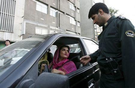File photo shows a policeman asking a woman wearing bright coloured clothes for her identification papers at a morals police checkpoint in Tehran