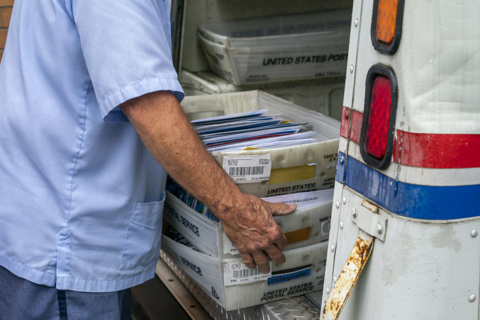 FILE - In this July 31, 2020, file photo, letter carriers load mail trucks for deliveries at a U.S. Postal Service facility in McLean, Va. The success of the 2020 presidential election could come down to a most unlikely government agency: the U.S. Postal Service. (AP Photo/J. Scott Applewhite, File)