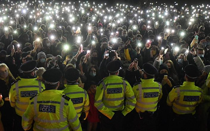 Police officers form a cordon as well-wishers turn on their phone torches as they gather at a band-stand where a planned vigil in honour of murder victim Sarah Everard was cancelled - AFP