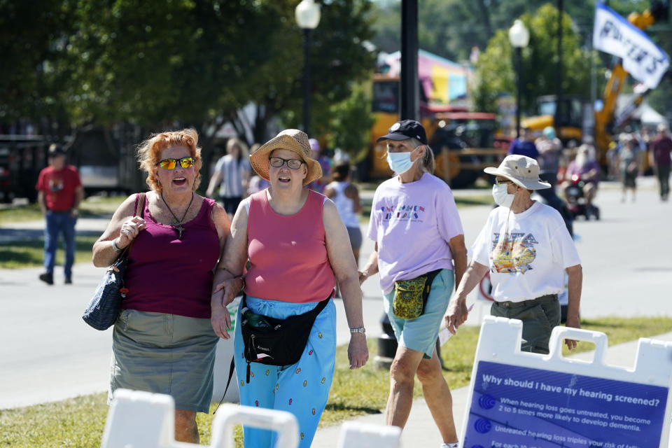 Visitors at the Iowa State Fair walk down a sidewalk near the grand concourse, Monday, Aug. 16, 2021, in Des Moines, Iowa. At the Iowa State Fair in Des Moines, where a million people are expected for the 11-day event, public health officials hope a vaccination station set up by pharmacists working for the Hy Vee food store chain will entice some of the vaccine-hesitant to get their shots. (AP Photo/Charlie Neibergall)