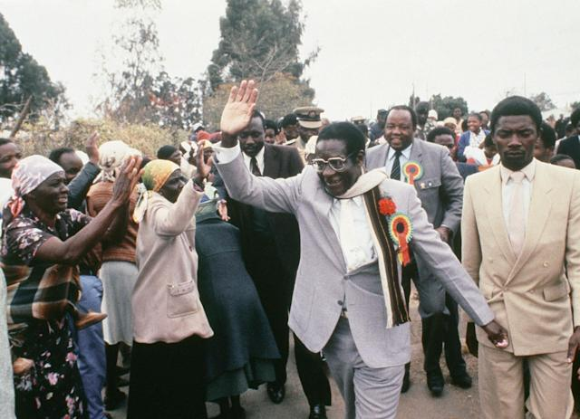 <p>Mugabe raises his hand to acknowledge supporters as he attended an election rally near Harare in July 1985. His ZANU party won a landslide victory in the country's first election since independence. (Photo: AP) </p>