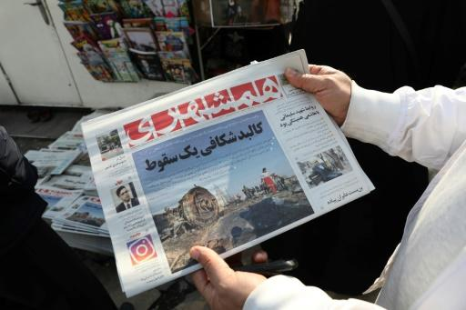 An Iranian holds a newspaper with a picture of the debris of the Ukrainian plane that crashed in Tehran on January 8, 2020, outside a news stand in the Islamic republic's capital