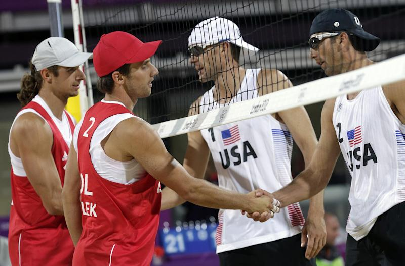 Grzegorz Fijalek (2) and Mariusz Prudel , left, of Poland are congratulated by Jacob Gibb and Sean Rosenthal, right, after Poland upset the USA during a beach volleyball match against the United States during the 2012 Summer Olympics, Monday, July 30, 2012, in London. (AP Photo/Dave Martin)