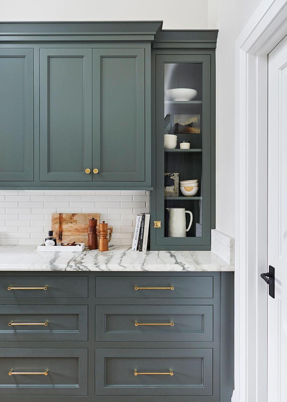 """While Henderson really does love everything about this kitchen, but the on-counter display cabinets are probably her favorite thing about it, along with the gooseneck faucets, and the vintage-inspired range. """"It's too hard to pick,"""" she says."""