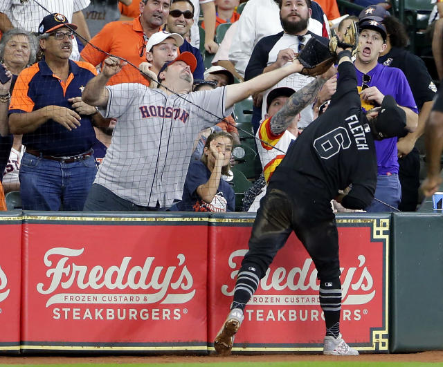 A fan nearly interferes with the catch for an out by Los Angeles Angels third baseman David Fletcher (6) on a foul hit by Houston Astros' Yuli Gurriel during the first inning of a baseball game Sunday, Aug. 25, 2019, in Houston. (AP Photo/Michael Wyke)