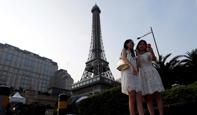 Visitors take a selfie in front of a replica of the Eiffel Tower in Macau. Photo: Reuters