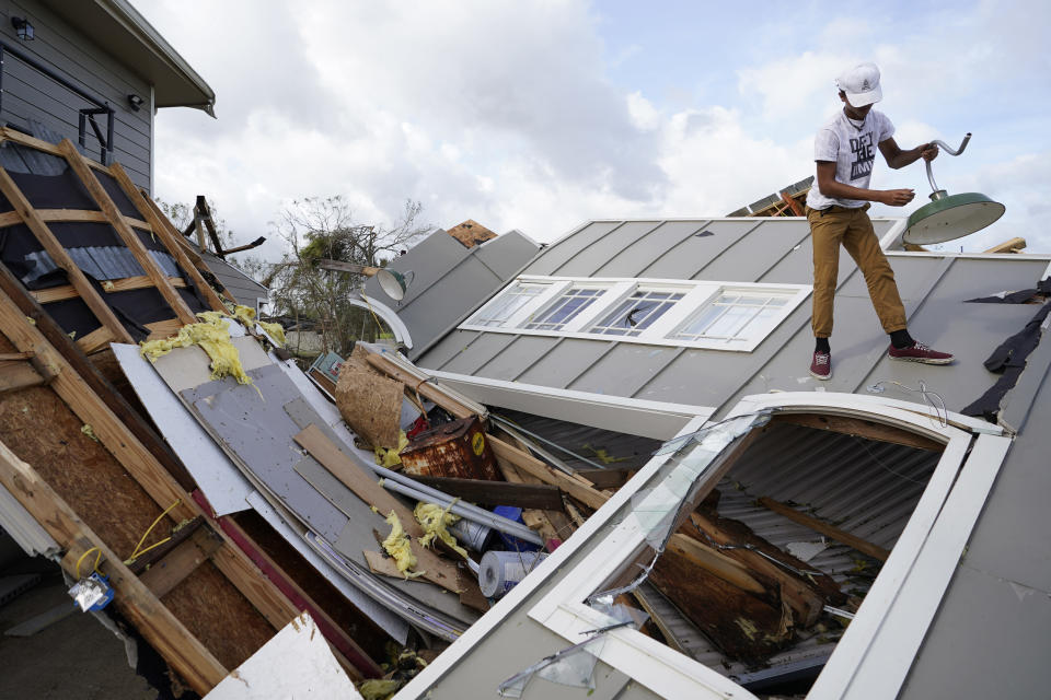 Jeremy Hodges removes a light from his family's destroyed storage unit in the aftermath of Hurricane Ida, Monday, Aug. 30, 2021, in Houma, La. (AP Photo/David J. Phillip)