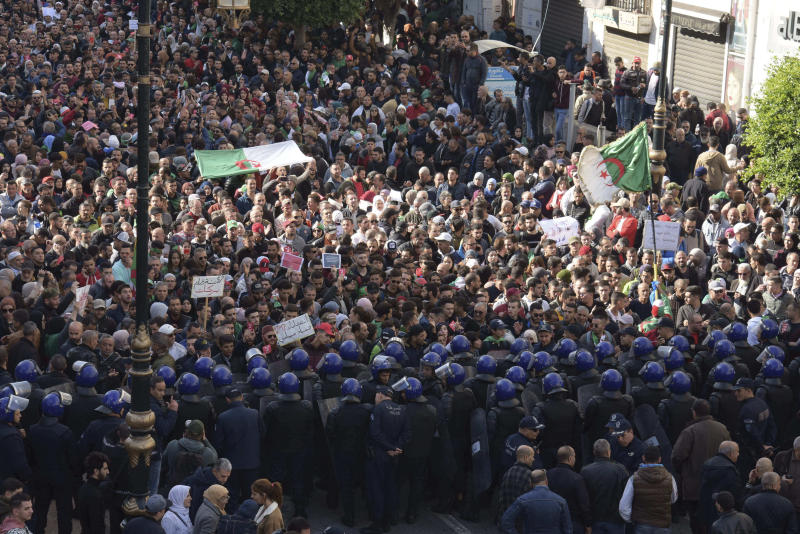 Algerian demonstrators take to the streets in the capital Algiers to protest against the government and reject the upcoming presidential elections, in Algeria, Wednesday, Dec. 11, 2019. Algeria's powerful army chief promises that a presidential election on Thursday will define the contours of a new era for a nation where the highest office has stood vacant for eight months. The tenacious pro-democracy movement which forced leader Abdelaziz Bouteflika to resign after 20 years in power doesn't trust the confident claim and is boycotting the vote. (AP Photo/Toufik Doudou)