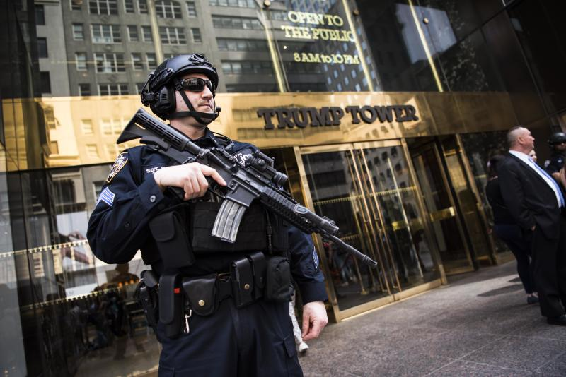An armed police officer stands guard at the entrance of Trump Tower on April 13. Extra security measures at the building have been a hassle for residents.  (Damon Dahlen/HuffPost)