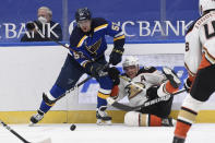 Anaheim Ducks' Jakob Silfverberg (33) falls to the ice as he works against St. Louis Blues' David Perron (57) for the puck during the second period of an NHL hockey game Friday, March 26, 2021, in St. Louis. (AP Photo/Joe Puetz)