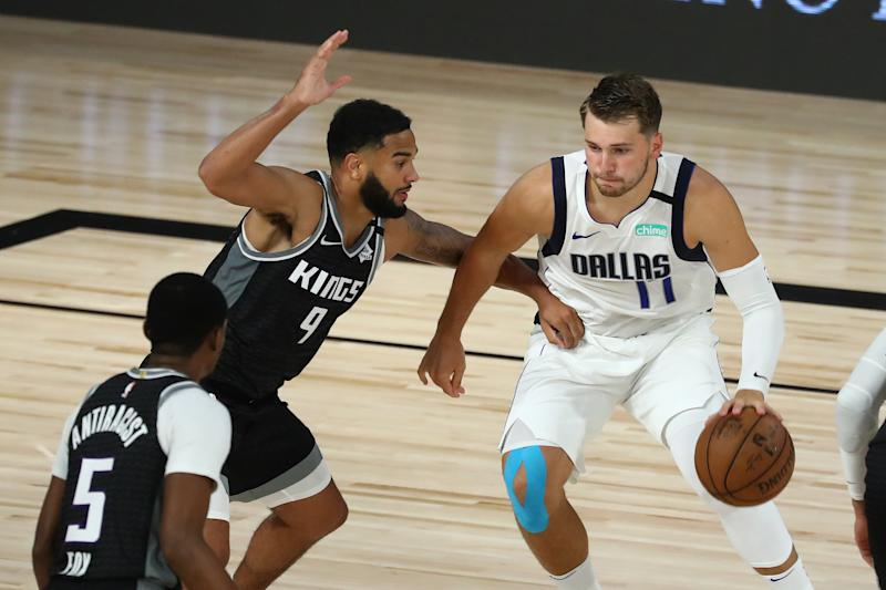 LAKE BUENA VISTA, FLORIDA - AUGUST 04: Luka Doncic #77 of the Dallas Mavericks drives against Cory Joseph #9 and De'Aaron Fox #5 of the Sacramento Kings in the second half of a NBA basketball game at HP Field House at ESPN Wide World Of Sports Complex on August 4, 2020 in Lake Buena Vista, Florida. NOTE TO USER: User expressly acknowledges and agrees that, by downloading and or using this photograph, User is consenting to the terms and conditions of the Getty Images License Agreement. (Photo by Kim Klement-Pool/Getty Images)