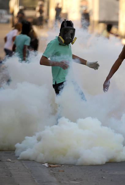 A Bahraini anti-government protester kicks at tear gas canisters fired by riot police in Sitra, Bahrain, on Wednesday, March 27, 2013. Clashes erupted after the politically charged funeral of Jaffar al-Taweel, 35, who relatives and rights activists say died from excessive tear gas inhalation. (AP Photo/Hasan Jamali)