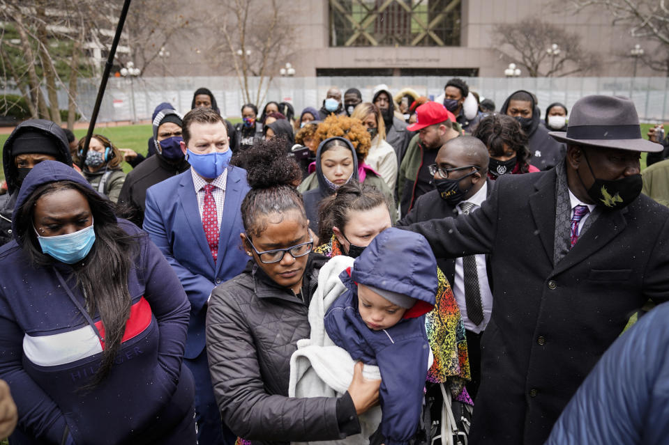 Chyna Whitaker, center, holds her son Daunte Jr., as she walks up to microphones to speak during a news conference, Tuesday, April 13, 2021, in Minneapolis. The father, Daunte Wright, 20, was shot and killed by police Sunday after a traffic stop in Brooklyn Center, Minn. (AP Photo/John Minchillo)