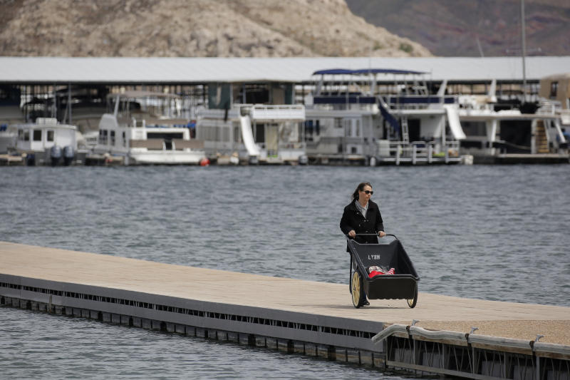FILE - In this Monday, March 23, 2020, file photo, a woman removes items before the Las Vegas Boat Harbor closes at the Lake Mead National Recreation Area near Boulder City, Nev. As the coronavirus pandemic continues, the National Park Service is testing public access at several parks across the nation, including Nevada, with limited offerings and services.   (AP Photo/John Locher, File)