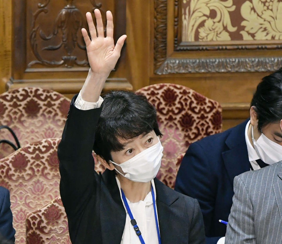 FILE - In this Thursday, Feb. 25, 2021, file photo, Makiko Yamada, public affairs official of Japanese Prime Minister Yoshihide Suga's cabinet, raises her hand during a parliamentary session at the lower house in Tokyo. Yamada has resigned Monday, March 1, 2021 after she acknowledged she had a 70,000 yen ($700) dinner paid for by a broadcaster. The broadcaster in question employs Suga's son, Seigo Suga.(Yoshitaka Sugawara/Kyodo News via AP, File)