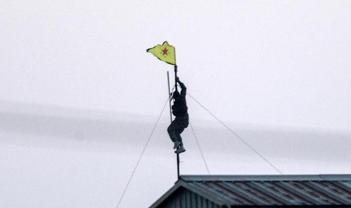 A Kurdish YPG fighter unfurls their flag at the Akcakale crossing gate between Turkey and Syria, in Sanliurfa province on June 15, 2015 (AFP Photo/Bulent Kilic)