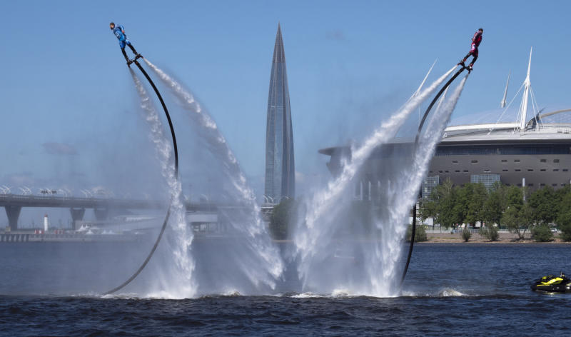 Members of the Russian hydroflight team perform during the Day of Russia celebration in St.Petersburg, Russia, Friday, June 12, 2020, with business tower Lakhta Centre, the headquarters of Russian gas monopoly Gazprom and Gazprom Arena soccer stadium in the background. (AP Photo/Dmitri Lovetsky)