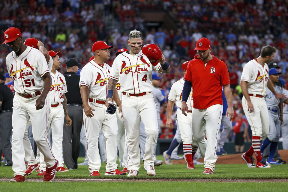 St. Louis Cardinals' Yadier Molina, center, walks toward first base as the rest of his teammates walk back to the dugout after a bench-clearing argument after he was hit by pitch during the second inning of a baseball game against the Chicago Cubs, Saturday, Sept. 28, 2019, in St. Louis. (AP Photo/Scott Kane)