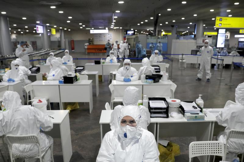 Russian medical experts wait to check passengers arriving from foreign countries at Sheremetyevo airport outside Moscow, Russia, Thursday, March 19, 2020. Authorities in Russia are taking vast measures to prevent the spread of the disease in the country. The measures include closing the border for all foreigners, shutting down schools for three weeks, sweeping testing and urging people to stay home. For most people, the new coronavirus causes only mild or moderate symptoms. For some it can cause more severe illness. (AP Photo/Pavel Golovkin)