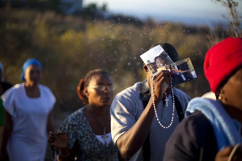 In this Feb. 8, 2014 photo, Christian pilgrims holding a rosary and photographs is sprinkled in holy water during a religious gathering in the village of Bois-Neuf, Haiti. Some brought photos of sick family members in hopes that their prayers will rid them of illness. (AP Photo/Dieu Nalio Chery)
