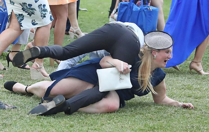 Racegoers tangled up on the grass during the 2016 Melbourne Cup at Flemington Racecourse.