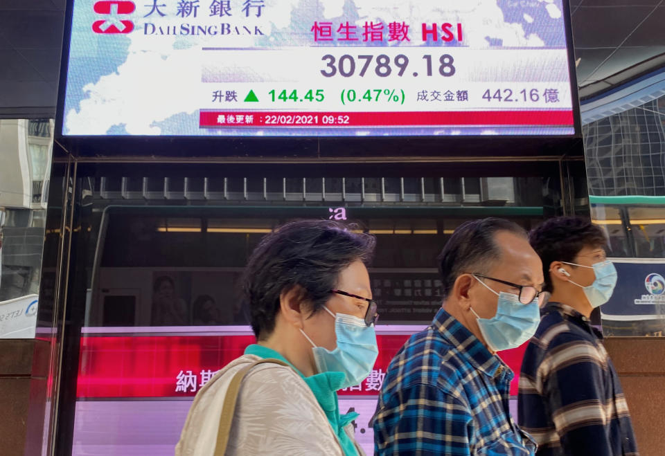 People walk past a bank's electronic board showing the Hong Kong share index in Hong Kong Monday, Feb. 22, 2021. Asian shares were mixed on Monday as hopes for a recovery from the coronavirus pandemic with the global rollout of vaccines were countered by worries about inflation and continuing economic damage. (AP Photo/Vincent Yu)