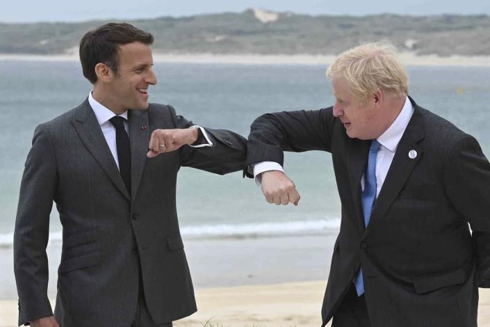 Britain's Prime Minister Boris Johnson, right greets French President Emmanuel Macron prior to the Leaders official welcome and group photo session, during the G7 summit, in Carbis Bay, Cornwall, England, Friday, June 11, 2021. (Leon Neal/Pool Photo via AP)