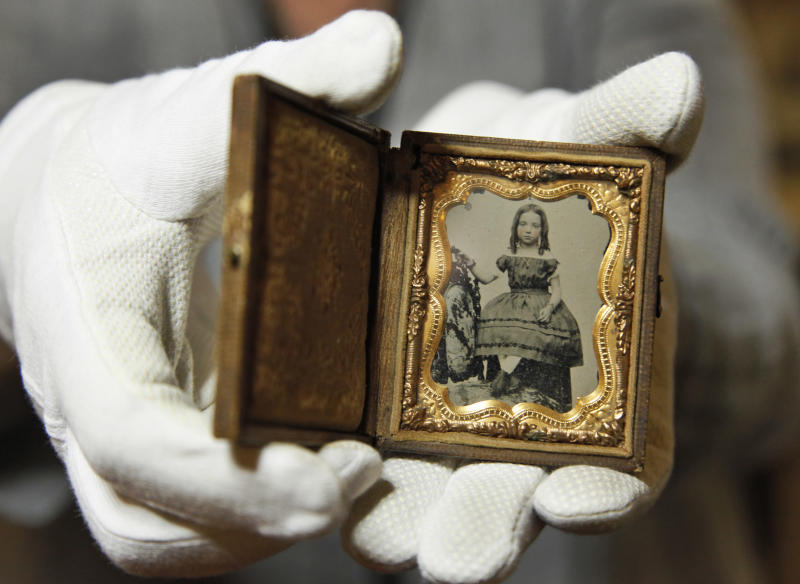 Ann Drury Wellford, manager of Photographic Services for The Museum of the Confederacy, a Civil War battlefield photos at the museum in Richmond, Va., Friday, May 25, 2012. Private Thomas W. Timberlake of Co. G, 2nd Virginia Infantry found this child's portrait on the battlefield of Port Republic, Virginia, between the bodies of a Confederate soldier and a Federal soldier. Eight photographs are publicly releasing the images in the admittedly remote chance a descendant might recognize a facial resemblance or make a connection the battlefields where they were found. (AP Photo/Steve Helber)