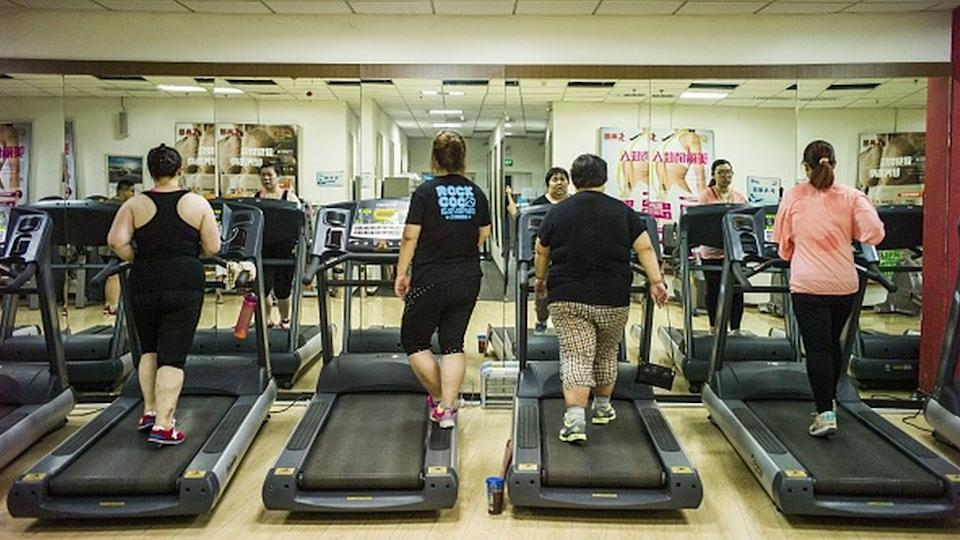 Four people use treadmills at the Aimin Fat Reduction Hospital in Tianjin, China, in 2015