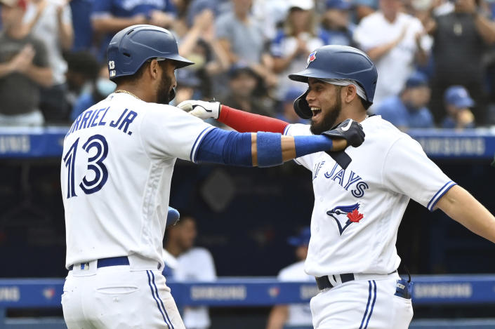 Toronto Blue Jays' Breyvic Valera celebrates his two-RBI home run with Lourdes Gurriel Jr. in the fourth inning of a baseball game against the Oakland Athletics in Toronto on Saturday, Sept. 4, 2021. (Jon Blacker/The Canadian Press via AP)