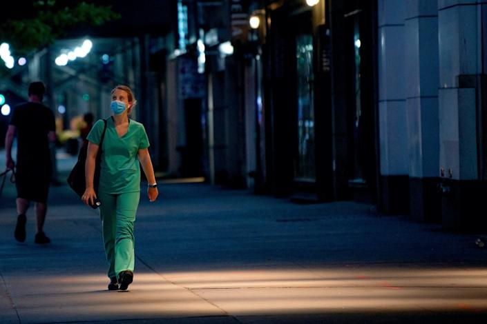 A medical worker walks down a New York street on May 29, 2020.