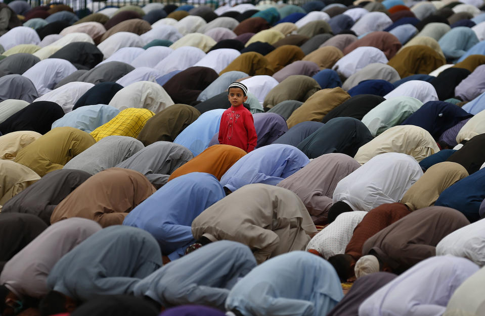 A Muslim boy stands beside his father performing an Eid al-Fitr prayer along with others at a ground in Rawalpindi, Pakistan, Thursday, May 13, 2021. Millions of Muslims across the world are marking a muted and gloomy holiday of Eid al-Fitr, the end of the fasting month of Ramadan, a usually joyous three-day celebration that has been significantly toned down as coronavirus cases soar. (AP Photo/Anjum Naveed)