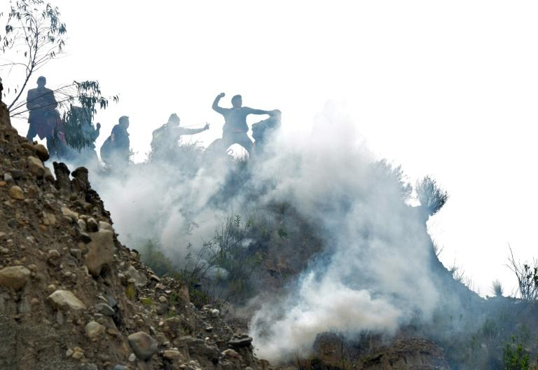Bolivian coca growers from Los Yungas region confront riot police agents within a tear gas cloud, during a protest against a bill that caps legal coca crops extensions in La Paz on February 21, 2017
