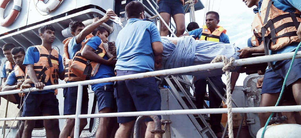 In this photo provided by Sri Lanka Navy, an injured crew member of the MT New Diamond, is transferred on stretcher to a navy vessel Thursday, Sept. 3, 2020, off Sangamankanda Point, Sri Lanka. A flotilla from Sri Lanka and India was escalating efforts to douse a fire raging on the oil tanker east of Sri Lanka for a second day Friday. The fire started Thursday in an engine room boiler on the MT New Diamond, leaving one crew member injured and one missing.(Sri Lanka Navy via AP)