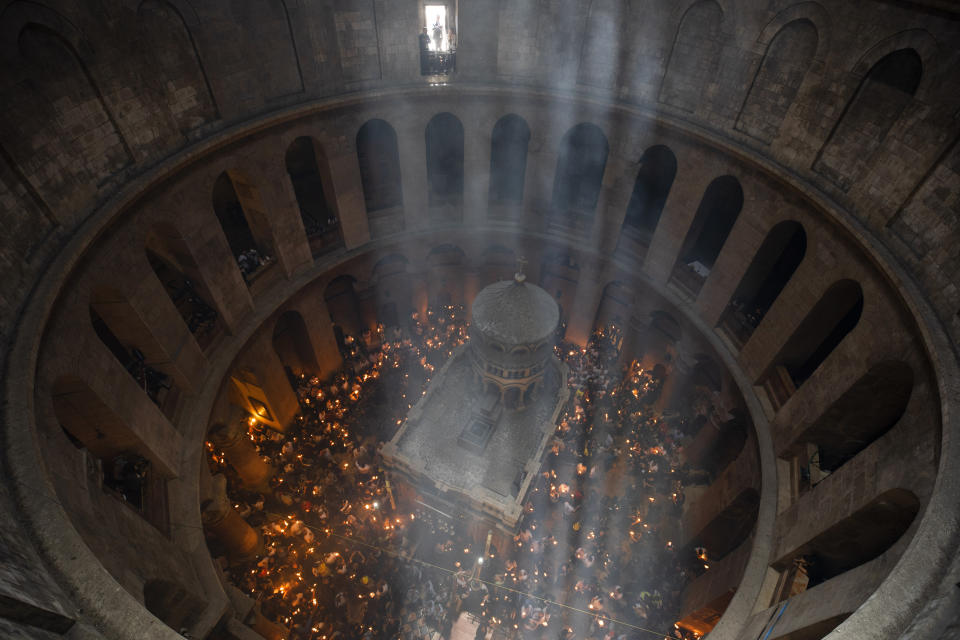 Christian pilgrims hold candles as they gather during the ceremony of the Holy Fire at Church of the Holy Sepulchre, where many Christians believe Jesus was crucified, buried and rose from the dead, in the Old City of Jerusalem, Saturday, May 1, 2021. Thousands of Christians have gathered in Jerusalem for the ancient fire ceremony that celebrates Jesus' resurrection. (AP Photo/Oded Balilty)