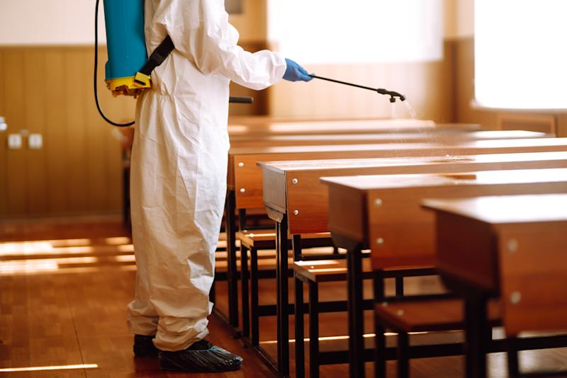 Man wearing protective suit disinfecting school class with spray chemicals to preventing the spread of coronavirus, pandemic in quarantine city. Disinfecting school desk. COVID-19.