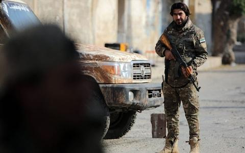 A Turkish-backed Syrian fighter stands at attention in the Syrian border town of Tal Abyad - Credit: BAKR ALKASEM/AFP via Getty Images