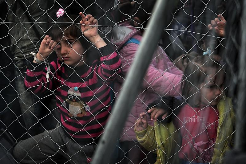 Children, behind a fence, wait to cross the Greek-Macedonian border along with other Syrian and Iraqis refugees near the village of Idomeni on February 27, 2016 (AFP Photo/Louisa Gouliamaki)