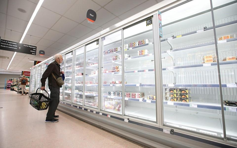 A shopper looks at empty shelves in the Co-Op supermarket, Harpenden - Reuters