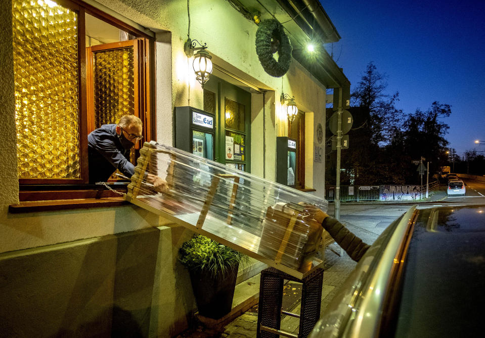 A box with food slides down to car from a window of the apple cider restaurant 'Zum Lahmen Esel' in Frankfurt, Germany, Thursday, Nov.5, 2020. Due to the new partial lockdown to avoid the coronavirus spread the restaurant which has been in operation since 1807 offers cider and food to go in a self-made drive through set up. (AP Photo/Michael Probst)