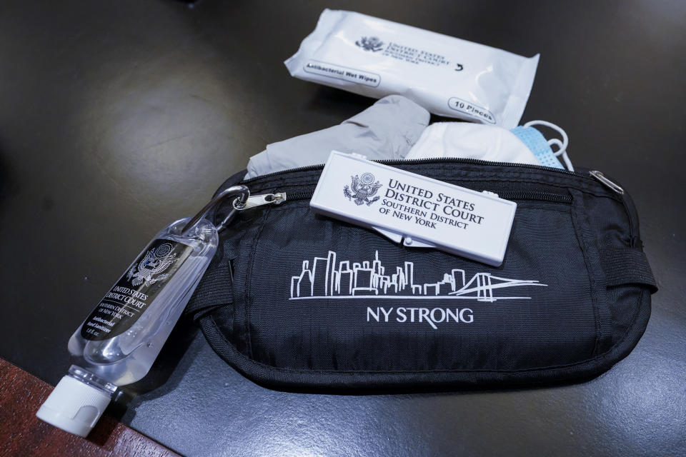 A pouch given to jurors containing face masks, gloves, disinfectant wipes, hand sanitizer and forehead thermometer strips is shown in a courtroom at a Manhattan federal courthouse, Friday, March 12, 2021, in New York. (AP Photo/Mary Altaffer)