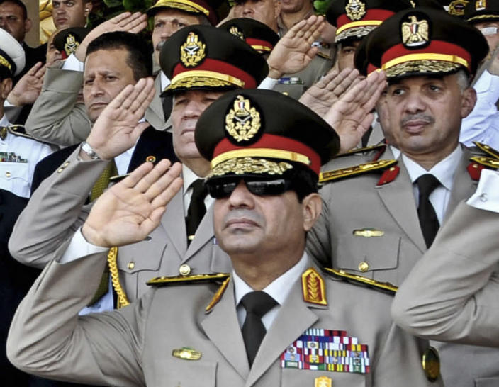 FILE - In this July 22, 2013, file photo released by the Egyptian Presidency, Defense Minister Gen. Abdel-Fattah el-Sissi, listens to the national anthem during a medal ceremony at a military base east of Cairo. The head of Egypt's military, Abdel-Fattah el-Sissi, is riding on a wave of popular fervor that is almost certain to carry him to election as president. Unknown only two years ago, a broad sector of Egyptians now hail him as the nation's savior after he ousted the Islamists from power, and the state-backed personality cult around him is so eclipsing, it may be difficult to find a candidate to oppose him if he runs. Still, if he becomes president, he faces the tough job of ruling a deeply divided nation that has already turned against two leaders.(AP Photo/Sheriff Abd El Minoem, Egyptian Presidency, File)
