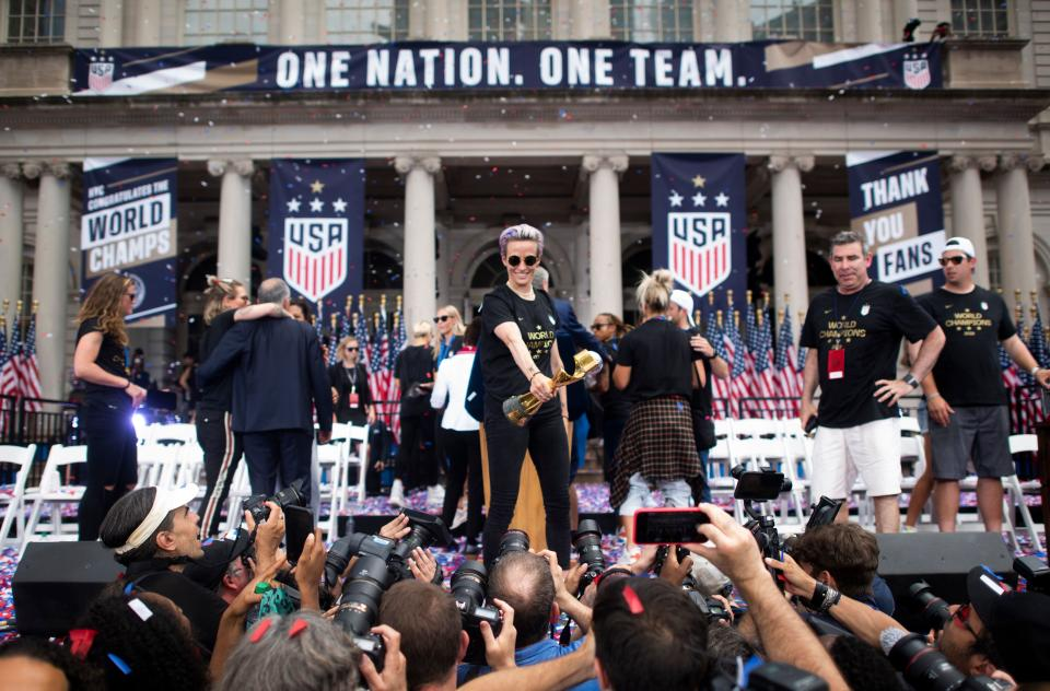 """USA women's soccer player Megan Rapinoe holds the trophy in front of the City Hall after  a ticker tape parade for the women's World Cup champions on July 10, 2019 in New York. - Amid chants of """"equal pay,"""" """"USA"""" and streams of confetti, the World Cup-winning US women's soccer team was feted by tens of thousands of adoring fans with a ticker-tape parade in New York on Wednesday. (Photo by Johannes EISELE / AFP)        (Photo credit should read JOHANNES EISELE/AFP/Getty Images)"""
