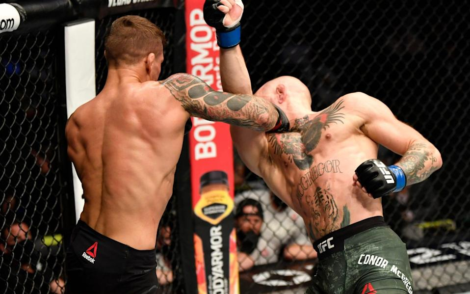 Dustin Poirier punches Conor McGregor of Ireland in a lightweight fight during the UFC 257 event  - Zuffa LLC