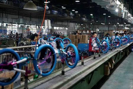 Employees work on the production line of Kent bicycles at Shanghai General Sports Co., Ltd, in Kunshan