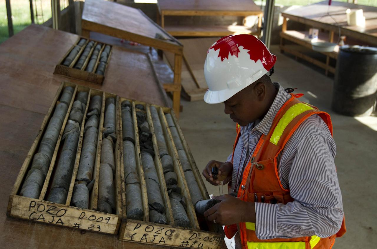 In this April 10, 2012 photo, geologist Francisque Pierre examines samples of stone to be examined for minerals and metals at an exploratory mine run by the SOMINE mining company in the department of Trou Du Nord, Haiti. Haiti's land may yet hold the solution to centuries of poverty: there is gold hidden in its hills, and silver and copper too. Now, two mining companies are drilling around the clock to determine how to get those metals out, and how much it might cost. (AP Photo/Dieu Nalio Chery)