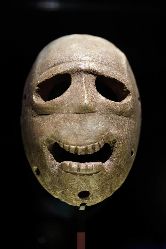 """In this Monday, March 10, 2014 photo, a 9,000 year-old mask is on display at the Israel Museum in Jerusalem. The exhibition called """"Face To Face"""" shows eleven stone masks, said to have been discovered in the Judean desert and hills near Jerusalem, which date back 9,000 years and offer a rare glimpse at some of civilization's first communal rituals. (AP Photo/Tsafrir Abayov)"""