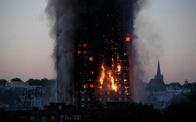 Flames and smoke billow as firefighters deal with a serious fire in a tower block at Latimer Road - Credit: Reuters