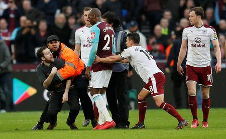 Soccer Football - Premier League - West Ham United vs Burnley - London Stadium, London, Britain - March 10, 2018 Fan is tackled by stewards after invading the pitch REUTERS/David Klein